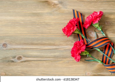 9 May background - red carnations and George ribbon on the wooden background, free space for text