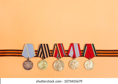 9 May background. St George's ribbon and medals of Great patriotic war on orange background. Heirloom.