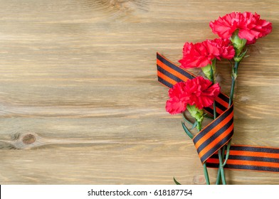 9 May card - red carnations and George ribbon lying on the wooden background with free space for text