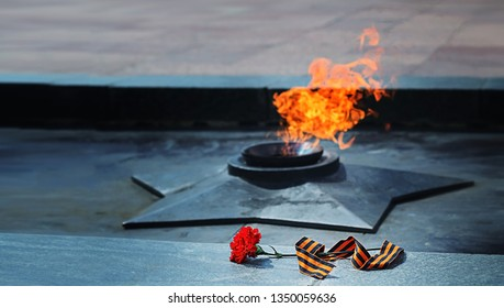9 May, Victory Day. George ribbon and carnations. holiday Victory Day. background for victory day may 9, 1945. eternal flame, monument and symbol of may 9, memory of war. soft focus