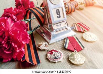9 May Victory Day holiday still life - vintage metal desk calendar with 9 May date, medals, George ribbon, red carnations bouquet - 9 May concept. Selective focus at the calendar