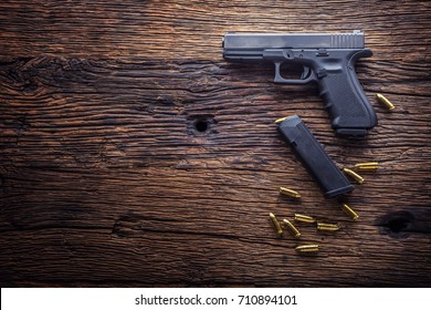 9 mm pistol gun and bullets strewn on the rustic oak table.