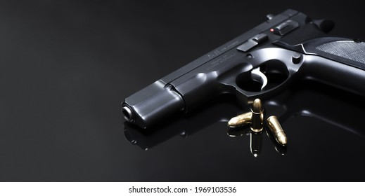 9 mm pistol with luger ammunitions on a black mirror base.