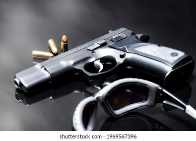 9 mm pistol with luger ammunitions and Shooting Safety Glasses on a black mirror base.