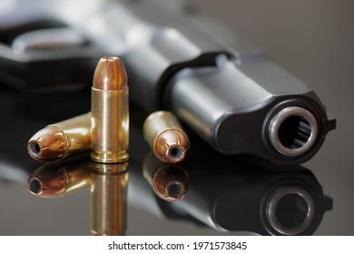 9 mm pistol with Luger JHP  ammunitions (dum-dum) on a mirror base.