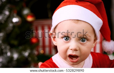 e5f4b0cfcf75 9 month old baby boy with shocked expression looking into the camera  wearing a Santa Claus