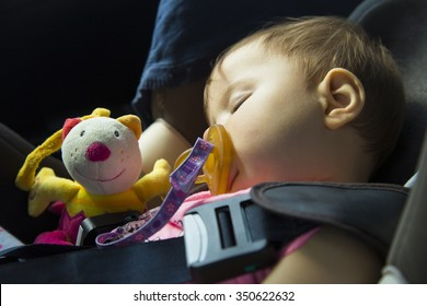 9 month old baby girl sleeping in the car seat with her puppet