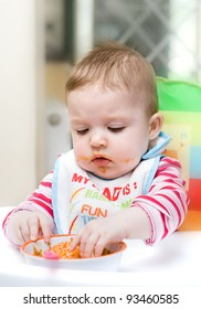 9 month old baby infant learning to eat by herself.