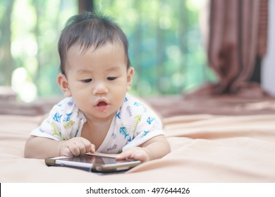 9 months Asian baby playing mobile phone