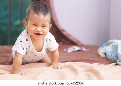9 months Asian baby playing on the bed