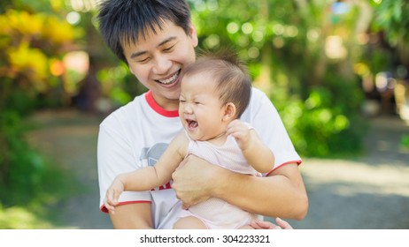 9 months baby laugh and big smile with her father in the garden. An emotional portrait of happy people.