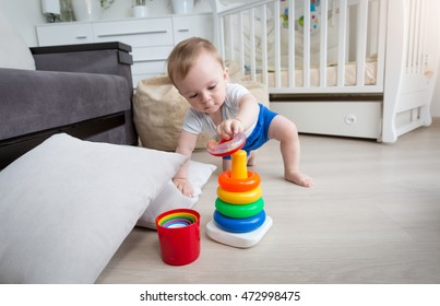 9 months old baby boy crawling on floor at living room and reaching for toy tower