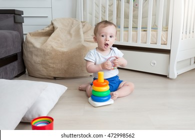 9 months old baby boy playing on floor and assembling toy tower