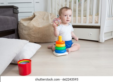 9 months old baby boy playing on floor with toy tower
