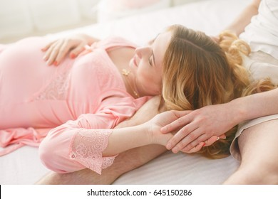 9 months pregnant woman awaiting baby.  Pregnancy and motherhood pretty pregnant in a pink dress. beautiful expectant mother in in delicate underwear. embrace couples.