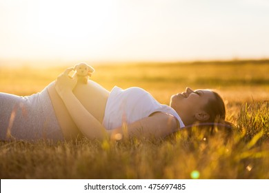 9 months pregnant woman lying on the ground and smiling. Waiting for baby. Pregnancy concept.