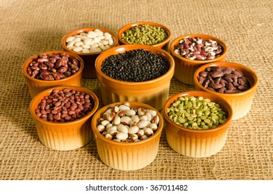 9 pottery containers with various types of pulse and legume seeds on a burlap background for 2016 year of the pulse