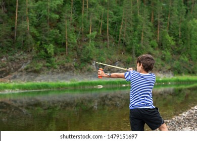 9 year old boy with a slingshot in his hands against the backdrop of a mountain landscape. The boy takes aim and is about to shoot a slingshot.