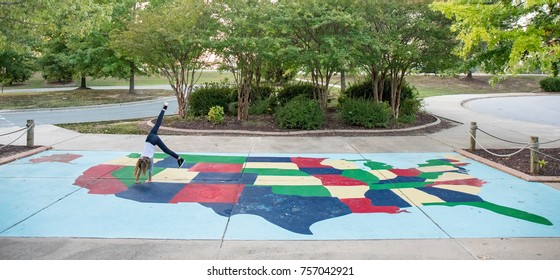 A 9 year old girl doing cart wheels across a map of the United States.