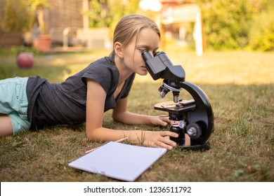 A 9 year old girl lies on the grass in the garden and looks into the eyepiece of a microscope. In front of her is a sheet of paper.