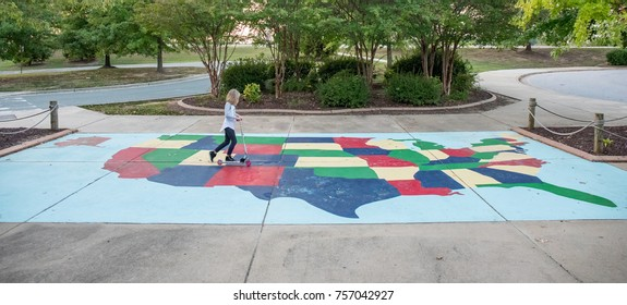A 9 year old girl riding a scooter across a map of the United States