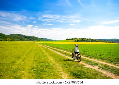 9 years girl going in bicycle across the fields in the sunny day, family cyclo holidays, summertime. Freedom, family, education, recreation and sport concept.