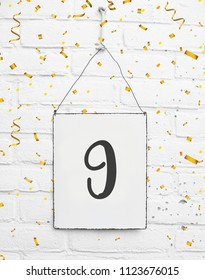 9 years old birthday party card text with golden confetti, number nine, metal plate white brick background
