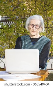 90 years old woman having a video call on a white notebook