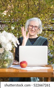 90 years old woman waving while having a a video call on a white notebook
