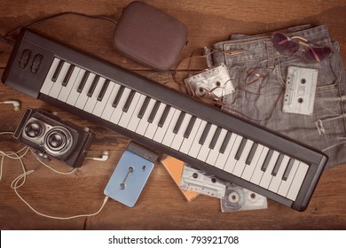90's vintage musician lifestyle accessories concept with keyboard instrument,old medium format camera,loudspeaker,compact cassettes,jeans,portable cassette player and sunglasses ,vintage filter.