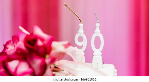 90th years old candles and cake in birthday party for the grandma, with pink background.