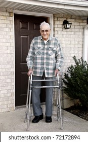 A 93 year old handicapped man, with a walker, standing outside in front of his apartment