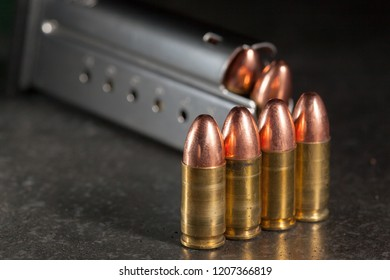 9mm ammunition lined up next to magazine.
