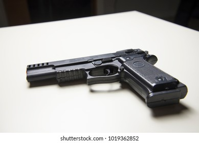 9mm automatic black pistol over a white table