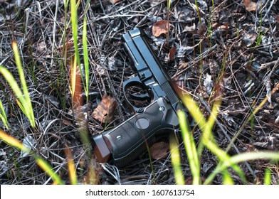 9mm Beretta black gun on the ground, killer equipment. Lost police weapon closeup. Special arming and ammunition scenery, pistol in grass