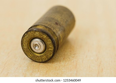 9mm bullet casing on a wooden table