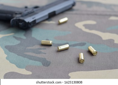 9mm bullets and pistol lie on camouflage green fabric. A set shooting range items or a self-defense kit