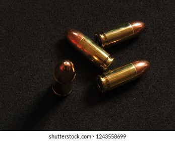 9mm copper ball ammo with brass shell on charcoal grey background