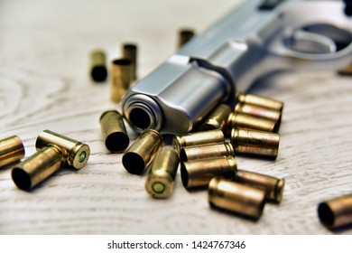 9mm gun with bullets on wooden background. Pistol and bullets.