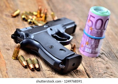 9mm handgun, bullets and roll of euro banknotes