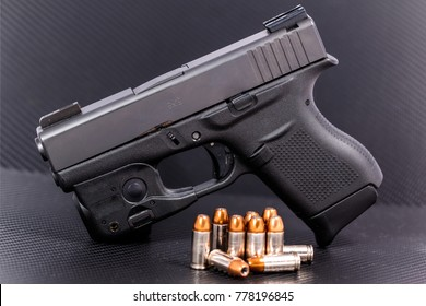 9mm hollow point cartridges with semi auto pistol on a carbon fiber background