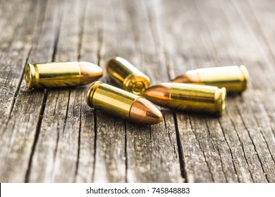 9mm pistol bullets on old wooden table.