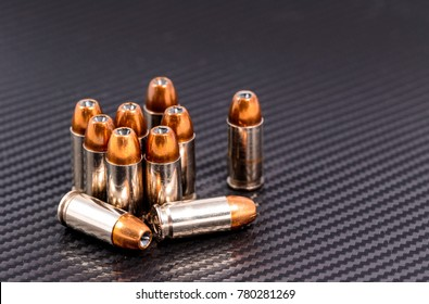 9mm pistol cartridges with hollow point bullets on a carbon fiber background