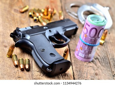 9mm pistol gun, bullets, handcuffs and roll of euro banknotes