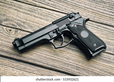 9mm pistol, Gun weapon series, Modern U.S. Army handgun M9 close-up on wooden background. (Color Processed)