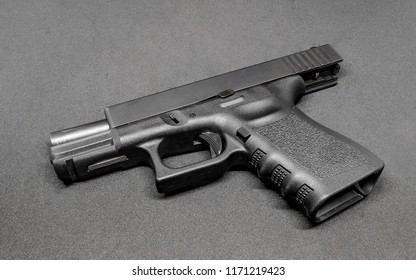 9mm pistol in locking slide placed on black floor