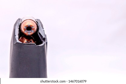 A 9mm pistol magazine loaded with hollow point bullets with extra room for text on a white background