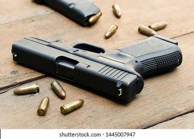 9mm semi-auto pistol, bullets and magazines placed on wooden table