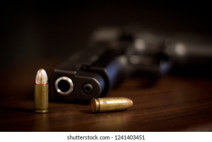9mm steel pistol and ammunition on a wooden ground with blurred background