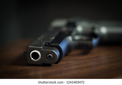 9mm steel pistol on a wooden surface with blurred background